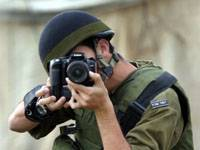 An Israeli soldier takes pictures during a military operation in the northern West Bank village or Birqin, near Jenin, 28 April 2006. Israel's incoming government under prime minister designate Ehud Olmert will work to give up territory in the occupied West Bank, according to a coalition agreement signed with the Labour party. AFP PHOTO/SAIF DAHLAH